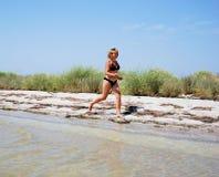 女孩运行海岸 免版税库存照片