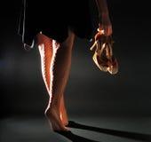 女孩运载拉丁凉鞋 免版税库存图片