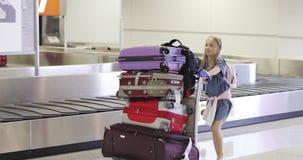 女孩运载有到达的行李的一个推车 股票录像