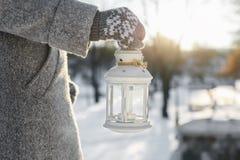 女孩运载有里面一个灼烧的蜡烛的灯笼 免版税图库摄影