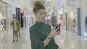 女孩运载的购物袋,当拿着智能手机在她的手上对录影电话活时放出她的从购物中心的最好的朋友- 股票视频
