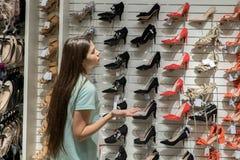 女孩选择她的鞋子 女孩不知道怎样选择 免版税库存照片