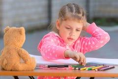 女孩选择有期望颜色的失去控制的画的铅笔 免版税图库摄影
