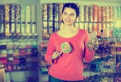 女孩选择焦糖和糖果 图库摄影