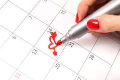 女孩递与铅笔图在日历的心脏形状为情人节 库存图片