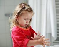 女孩递她小的洗涤物 免版税库存照片