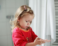 女孩递她小的洗涤物 免版税图库摄影