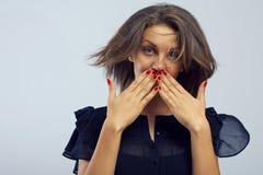 女孩递她隐藏的嘴惊奇的年轻人 免版税库存图片