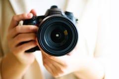女孩递拿着照片照相机,白色背景,拷贝空间 旅行和射击概念 免版税库存图片