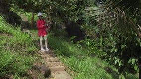 女孩通过热带公园走并且为自然股票英尺长度录影照相秀丽  股票视频