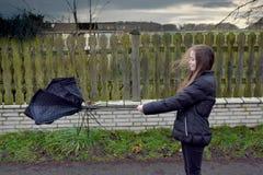 女孩通过风暴走,她的伞是残破的 库存图片