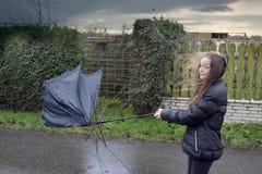 女孩通过风暴走,她的伞是残破的 图库摄影