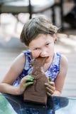 女孩采取巧克力兔宝宝的叮咬 免版税库存图片