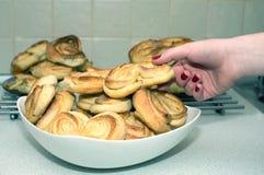 女孩采取从板材的鲜美开胃被烘烤的小圆面包 免版税库存照片