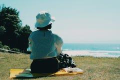 女孩野餐在海边庭院里 免版税库存照片