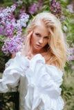 女孩金发碧眼的女人的画象有淡紫色灌木的 库存照片