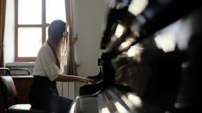 女孩钢琴演奏家在慢动作的窗口附近演奏在大平台钢琴的古典音乐 股票录像