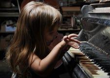 女孩钢琴使用 免版税库存图片