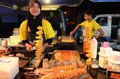 女孩销售在临时夜市场上油煎了土豆 免版税库存照片