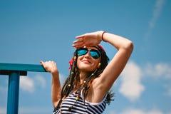 女孩镶边的礼服太阳镜微笑神色天空手 库存图片