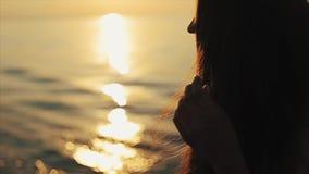 女孩长的棕色头发和日落反射在水中 股票视频