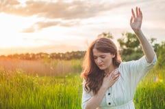 女孩闭上了她的眼睛,祈祷在领域在美好的日落期间 在信念的祷告概念折叠的手 库存图片