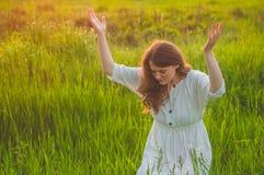 女孩闭上了她的眼睛,祈祷在领域在美好的日落期间 在信念的祷告概念折叠的手 免版税库存图片