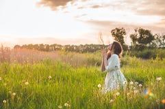 女孩闭上了她的眼睛,祈祷在领域在美好的日落期间 在信念的祷告概念折叠的手 免版税库存照片
