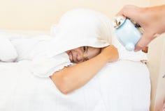 女孩闹钟有枕头的和被唤醒的覆盖物头 库存图片