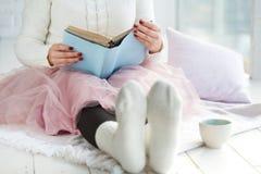 女孩阅读书在保留您的咖啡的毛线衣和温暖的袜子的床上手中在早晨 概念晴朗的春天心情 库存图片