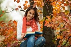 女孩阅读书在秋天公园 图库摄影