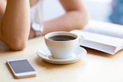 女孩阅读书和饮用的咖啡在咖啡馆 库存照片