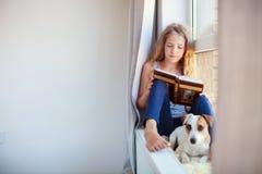 女孩阅读书在家 免版税库存图片