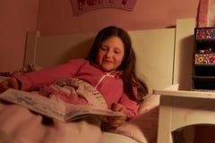 女孩阅读书在床上在晚上 免版税库存照片