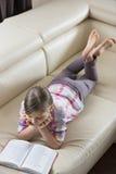 女孩阅读书大角度看法,当在家时说谎在沙发 免版税库存照片