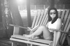 女孩阅读书室外在海滩 免版税库存照片