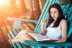 女孩阅读书室外在海滩 库存照片