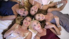 女孩集会,睡衣裤的微笑的女朋友与美好的构成在床上说谎并且获得看照相机的乐趣 股票视频
