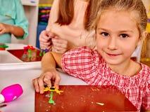 女孩雕刻在书桌上的彩色塑泥  库存图片