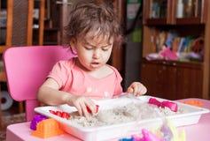 女孩雕刻在沙子外面在她的屋子里 免版税库存图片