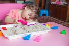 女孩雕刻在沙子外面在她的屋子里 免版税库存照片