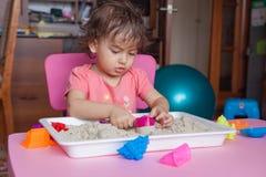 女孩雕刻在沙子外面在她的屋子里 库存图片