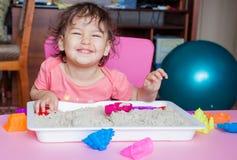 女孩雕刻在沙子外面在她的屋子里 库存照片