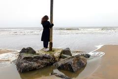 女孩雨海风冬天画象妇女微笑春天外套长的头发卷曲心情岸雪海滩秋天deadpan 库存图片
