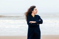 女孩雨海风冬天画象妇女微笑春天外套长的头发卷曲心情岸雪海滩 免版税库存图片
