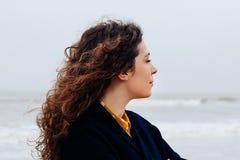 女孩雨海风冬天画象妇女微笑春天外套长的头发卷曲心情岸雪海滩 库存图片