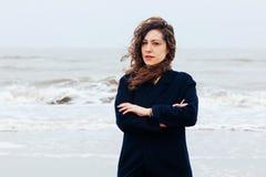 女孩雨海风冬天画象妇女微笑春天外套长的头发卷曲心情岸雪海滩 图库摄影
