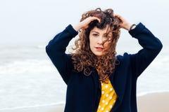 女孩雨海风冬天画象妇女微笑春天外套长的头发卷曲心情岸雪海滩 免版税库存照片