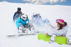 女孩雪飞溅三个年轻人 库存图片