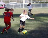女孩青年足球跑为球的足球运动员 免版税图库摄影